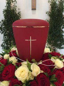 Urne in rot mit goldenem Kreuz und Zierstreifen